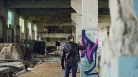 Male graffiti painter is creating abstract image with spray paint inside abandoned empty building. Old column is in. Male graffiti painter is creating abstract stock footage