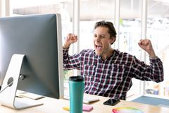 Male graphic designer celebrating success at desk in a modern office. Side view of happy Caucasian male graphic designer celebrating success at desk in a modern royalty free stock images