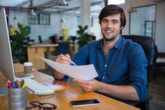 Male graphic designer at desk. Portrait of male graphic designer at desk in office stock image