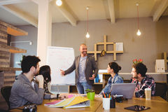Male graphic designer discussing chart on white board with coworkers. In the office Royalty Free Stock Image