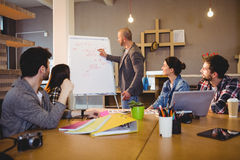 Male graphic designer discussing chart on white board with coworkers. In the office Stock Photo