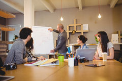 Male graphic designer discussing chart on white board with coworkers. In the office Royalty Free Stock Photo