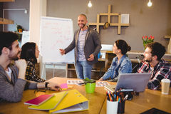 Male graphic designer discussing chart on white board with coworkers. In the office Royalty Free Stock Photos