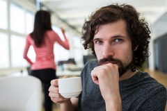 Male graphic designer holding coffee cup at desk royalty free stock images