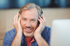Male graphic designer listening music on headphones Stock Image