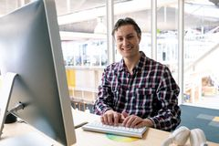Male graphic designer looking at camera while working on computer at desk in a modern office. Front view of happy Caucasian male graphic designer looking at stock images