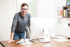 Male graphic designer looking smart. Portrait of a young Hispanic graphic designer leaning on his office desk and looking confident with a smile stock photos