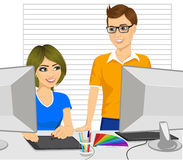 Male graphic designer partner helping his female colleague how to work with a graphic tablet Royalty Free Stock Photos