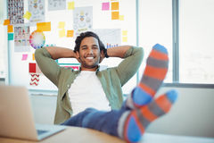 Male graphic designer relaxing with feet up at desk. In office stock photo