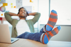 Male graphic designer relaxing with feet up at desk. In office royalty free stock photography