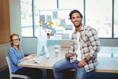 Male graphic designer sitting on desk with coworker in conference room. At office royalty free stock images