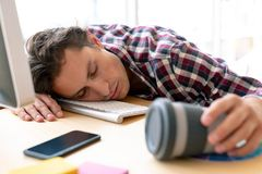 Male graphic designer sleeping on desk in a modern office. Front view of tired Caucasian male graphic designer sleeping on desk in a modern office stock images