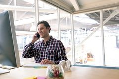 Male graphic designer talking on mobile phone at desk in a modern office. Side view of happy Caucasian male graphic designer talking on mobile phone at desk in a royalty free stock images