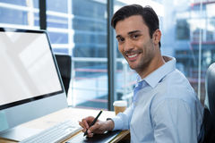 Male graphic designer using graphics tablet at desk. Portrait of male graphic designer using graphics tablet at desk in office royalty free stock photography