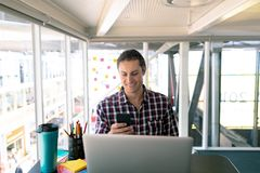 Male graphic designer using mobile phone while working on laptop at desk stock image
