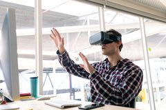 Male graphic designer using virtual reality headset at desk stock photos