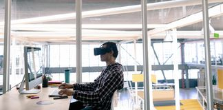 Male graphic designer using virtual reality headset while working on computer at desk. Side view of Caucasian male graphic designer using virtual reality headset royalty free stock photography