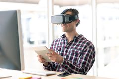 Male graphic designer using virtual reality headset while working on digital tablet at desk royalty free stock photos