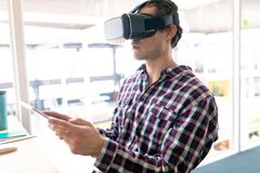 Male graphic designer using virtual reality headset while working on digital tablet at desk stock photo