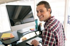 Male graphic designer working on computer at desk in office stock images