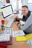 Male graphic designer working at desk. In the office stock image