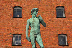 Male green antique statue and red brick building Stock Image