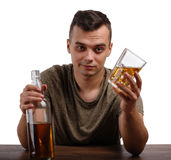 An adult boozed man showing a bottle of an alcoholic beverage, isolated on a white background. Alcoholism concept. royalty free stock photography