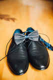 Male groom set of shoes and bow tien. A male groom set of shoes and bow tie on a wooden floorn Royalty Free Stock Images