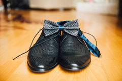 Male groom set of shoes and bow tien. A male groom set of shoes and bow tie on a wooden floorn Stock Image