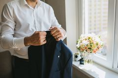Male groom in a white shirt is holding a blue wedding jacket in the morning. Horizontal Stock Photos