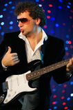 Male guitar player on stage Royalty Free Stock Photo