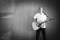 Male guitarist isolated against wall playing acoustic guitar Stock Image