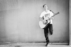 Male guitarist leaning aginst wall playing acoustic guitar Royalty Free Stock Photography