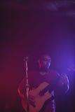 Male guitarist performing in concert. Confident male guitarist performing in concert Stock Photography