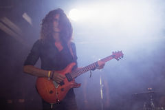 Male guitarist performing with curly hair at nightclub. Male guitarist with curly hair covering his face performing at nightclub Royalty Free Stock Photos