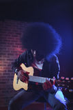 Male guitarist performing at music concert. Male guitarist with frizzy hair performing at music concert Royalty Free Stock Image