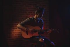 Male guitarist performing in nightclub. Confident male guitarist performing in nightclub Stock Photos