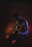 Male guitarist performing in nightclub. Young male guitarist performing in nightclub Royalty Free Stock Photography