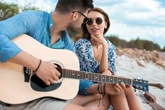 Male guitarist playing acoustic guitar and sitting with girlfriend. Outdoors stock images
