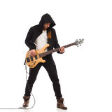 Male guitarist plays the bass giutar. Royalty Free Stock Image