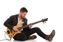 Male guitarist plays the bass guitar Royalty Free Stock Image
