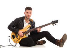 Male guitarist sitting on the floor. Royalty Free Stock Images