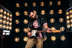 Male guitarist on stage with decorations of lights. Male bearded guitarist in black leather jacket on the stage with the decorations of lights. Performer with Royalty Free Stock Photography