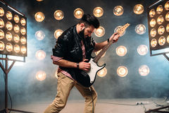 Male guitarist on stage with decorations of lights. Male bearded guitarist in black leather jacket on the stage with the decorations of lights. Performer with Royalty Free Stock Photos