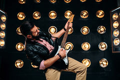 Male guitarist on stage with decorations of lights. Male bearded guitarist in black leather jacket on the stage with the decorations of lights. Performer with Stock Images