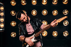 Male guitarist on stage with decorations of lights Royalty Free Stock Image