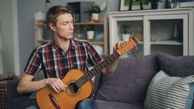 Male guitarist is tuning acoustic guitar checking sound touching strings sitting on sofa at home. Youth culture and. Lifestyle, stylish apartments and music stock video footage