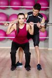 Male Gym Instructor Helping Woman Carrying Weights. Handsome Male Gym Instructor Helping Pretty Young Woman Carrying Weights at her Back While Looking at the Stock Photos