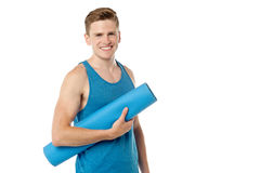 Male gym instructor holding blue mat. Smiling male fitness instructor holding blue mat Stock Photo
