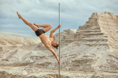 Male gymnast does tricks on a pylon. Male gymnast does tricks on a pylon in the desert on the sand Royalty Free Stock Images